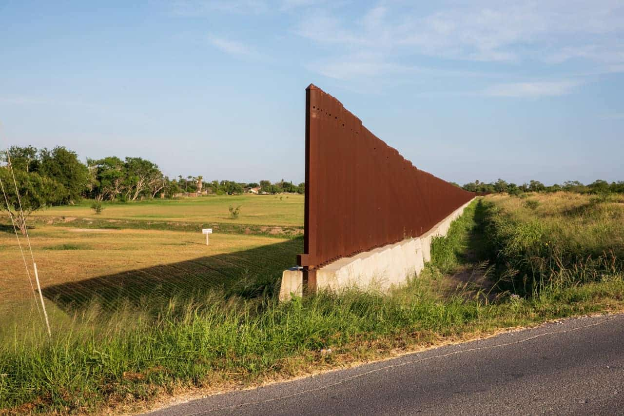 A break in the border fence leaves room for a road to pass through in Brownsville, Texas
